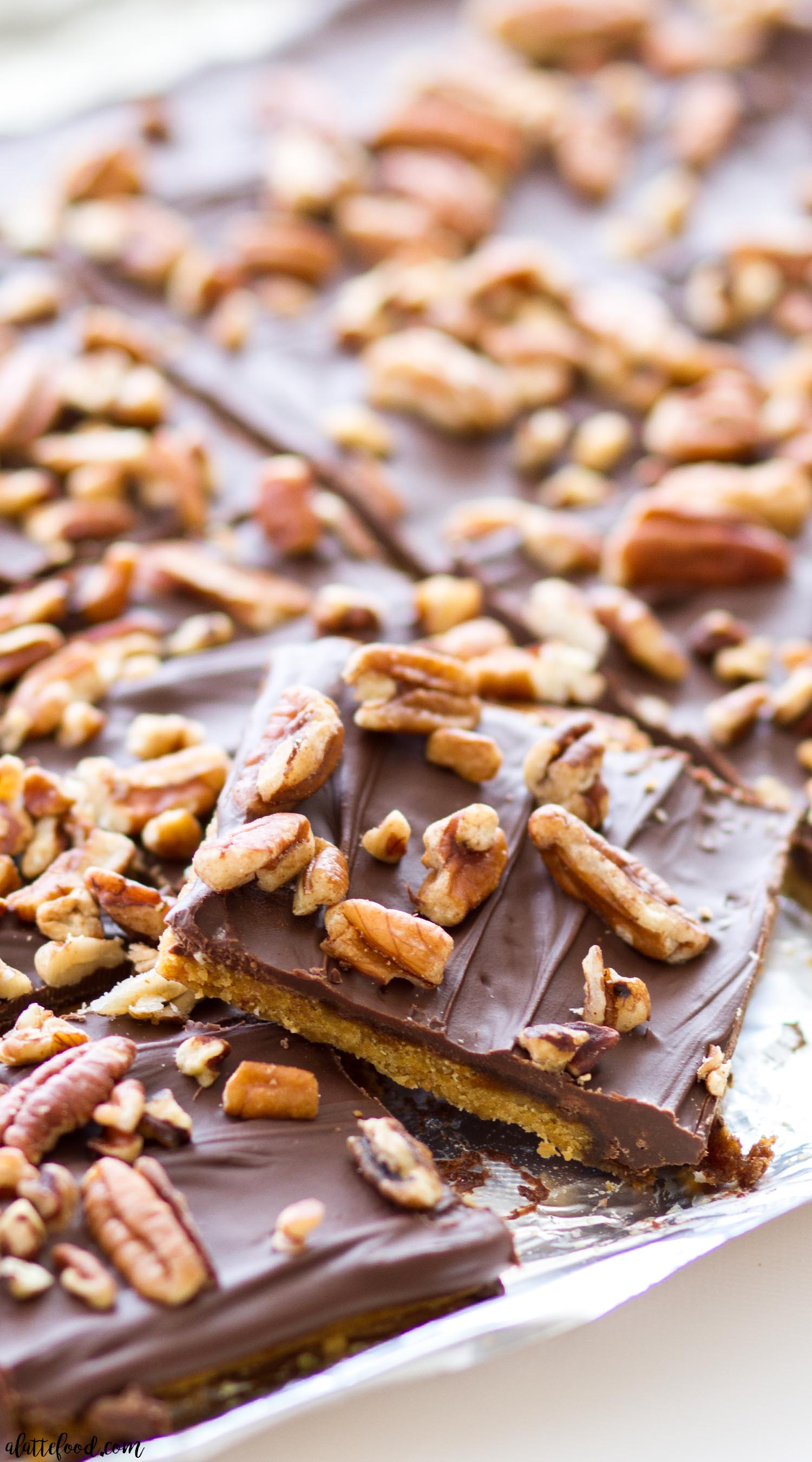 Pumpkin Spice Cracker Toffee with chocolate and pecans on aluminum foil